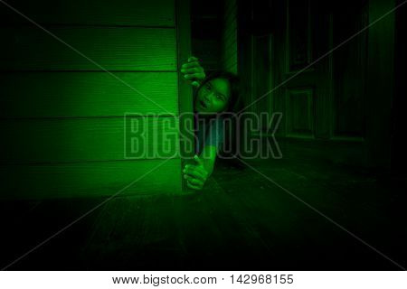 Woman reaching hand for help from being drag of something behind the door