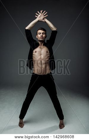sexy young fashion man wearing a black shirt unbuttoned