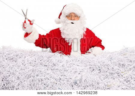 Smiling Santa Claus standing in a pile of shredded paper and holding a pair of scissors isolated on white background