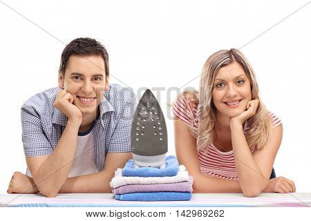 Young smiling couple posing by an iron and a pile of clothes isolated on white background