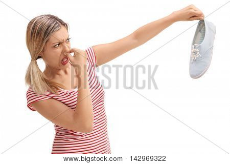 Disgusted woman holding a stinky shoe isolated on white background