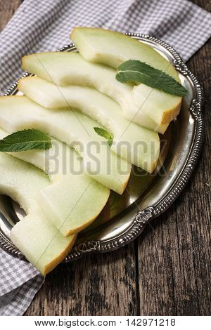Fresh melons sliced and mint on wooden table healthy food