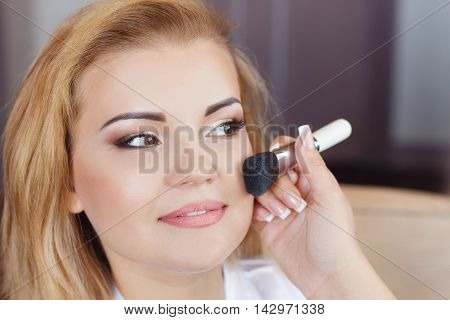 Woman is doing professional makeup. Bride doing makeup in the morning in room. Wedding makeup. Makeup artist doing makeup for beautiful girl. Morning of the bride