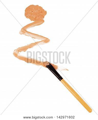 Close-up of makeup brush with smeared liquid foundation on white background.