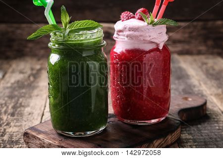 Healthy green fresh fruit and vegetable juice green and pink smoothie on wooden table
