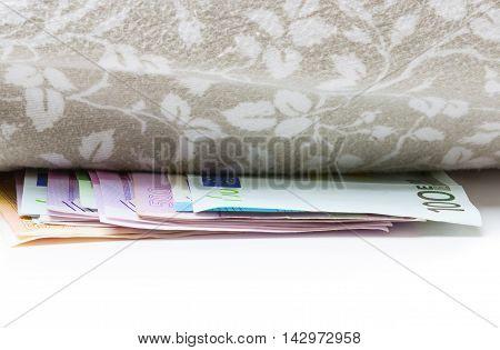 Euro bank notes are under pillow hiding