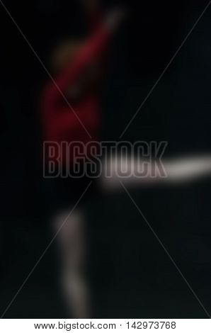 Contemporary dancer wearing red performance abstract blur background with shallow depth of field