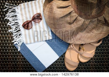 Concept of flat lay summer accessories of white, blue and beige Turkish towel, sunglasses and straw hat on rattan lounger with blue swimming pool as background.