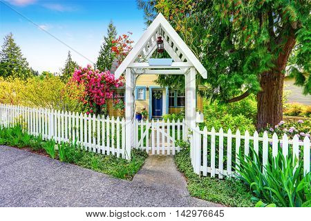 Small Yellow House Exterior With White Picket Fence