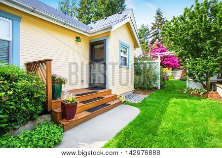 Yellow House Backyard Area With Small Porch And Stairs