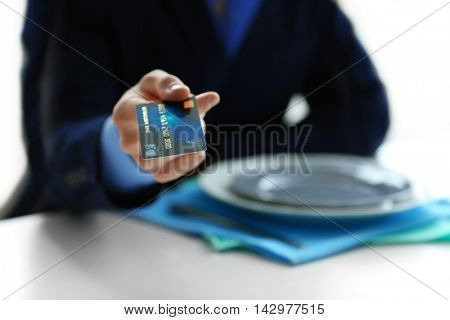 Businessman paying restaurant bill with credit card