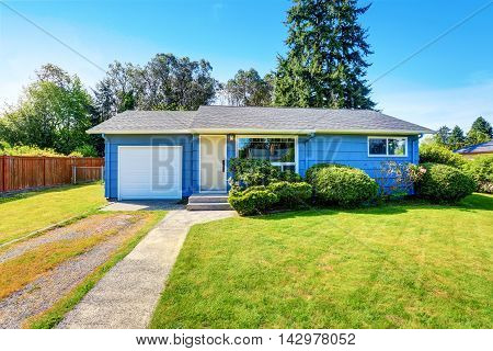 Small Cute Blue House With Driveway And Trimmed Hedges.
