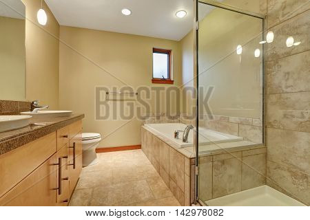 Bathroom Interior In Beige Tones With Vanity Cabinet With Granite Counter Top.