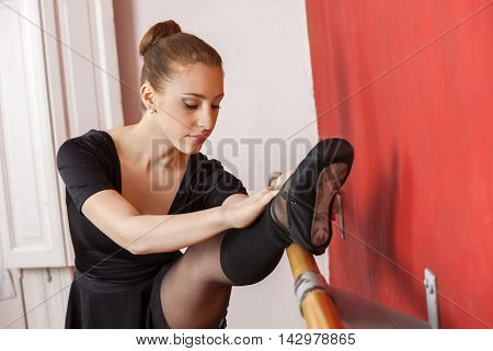 Young Ballerina Stretching Her Leg At Barre