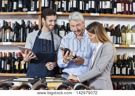 Couple With Wine Bottle Standing By Salesman Holding Digital Tab