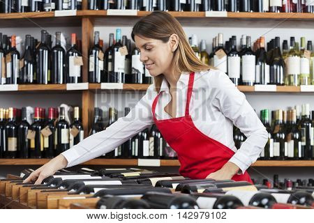 Saleswoman Arranging Wine Bottles In Rack At Winery