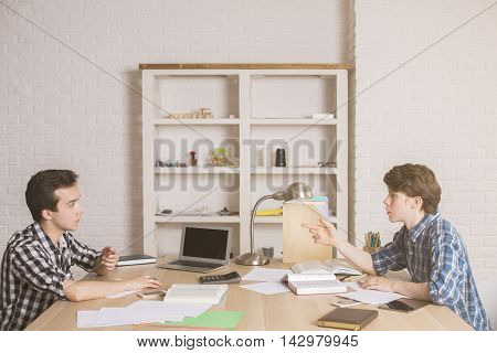 Two college students studying for exam at large wooden desk with blank laptop calculator homework and other stuff on white brick wall background. Mock up