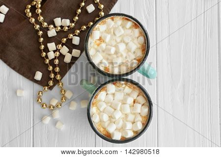 Mugs of hot cocoa drink with marshmallows on table