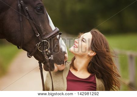 brunette woman and her brown horse in nature