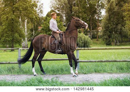 man riding his brown horse at a farm