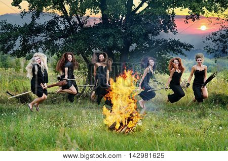witches fly on brooms near a campfire in the meadow
