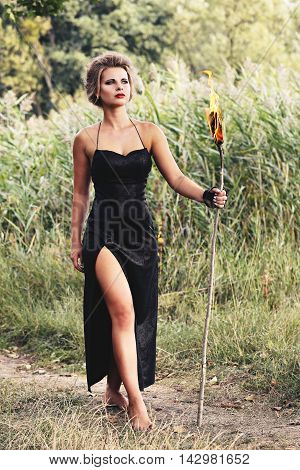 women are holding with torches in the forest