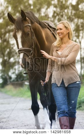 blond woman walking with her horse on farmland