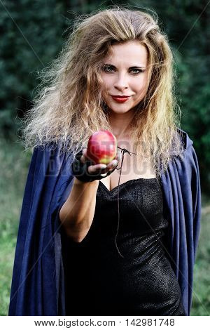 Young beautiful woman holds out her hand with an apple