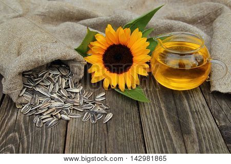 Sunflower, sunflower seeds in a bag and oil on a table in a garden