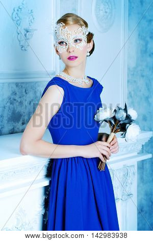 Elegant lady wearing elegant evening dress standing by a fireplace in a room with classical vintage interior. Jewellery. Fashion shot. Hairstyle.