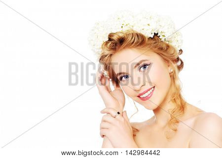 Beautiful young woman with natural make-up and wreath of white flowers on her head smiling at camera. Summer, spring inspiration. Beauty, fashion, cosmetics. Isolated over white.