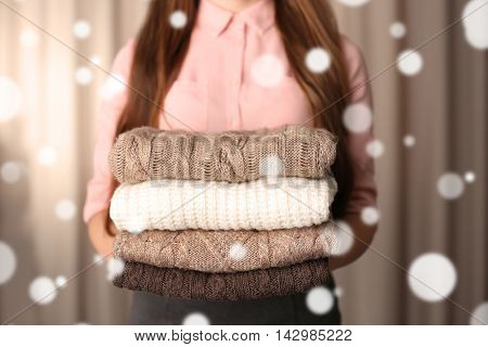 Stack of knitted clothes in female hands closeup. Snow effect