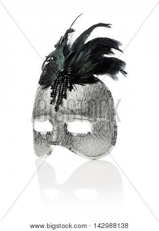 Silver color plastic mask with sequins and feathers isolated on white with reflection.