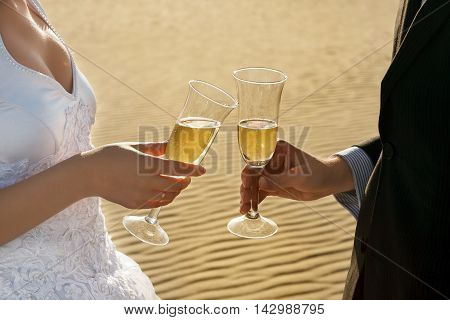 bride and groom are holding champagne glasses on a background of sand