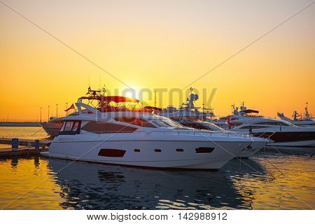 Extra Large Luxury yachts rest in the port at sunset