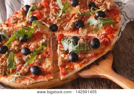 Sliced Pizza With Tuna, Olives And Arugula Close-up. Horizontal