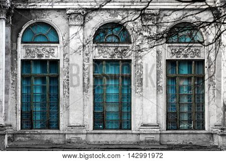 Facade of old abandoned building with three large arched windows of blue glass and columns. Monochrome background