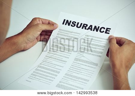 closeup of a young caucasian man sitting at a white table reading the terms of an insurance