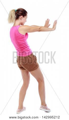 back view of woman pushes wall.  Isolated over white background. Rear view people collection. backside view of person. Sport blond in brown shorts pushes away someone.