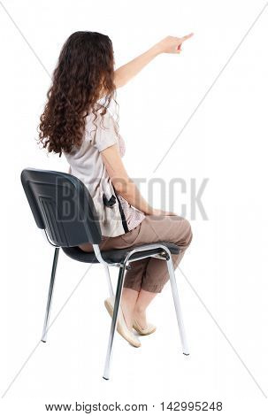 back view of young beautiful  woman sitting on chair and pointing.  girl  watching. Rear view people collection. Long-haired curly girl sitting on a chair and pointing to something interesting.