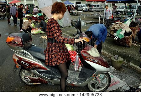 Ao Ping China - September 14 2006: Woman on her motorcycle shops for food at the big outdoor marketplace