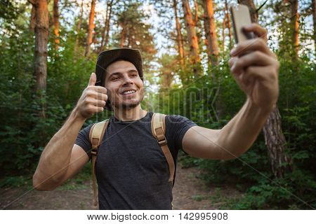 Man takes a picture of himself on the phone in the forest. showing a thumbs up and smiling.