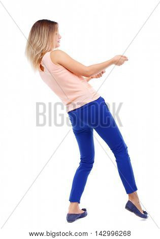 back view of standing girl pulling a rope from the top or cling to something. girl  watching. Rear view people collection.  backside view of person.  Isolated over white background. The blonde in a