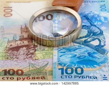 Russian money: 100 rubles banknote and magnifier shallow DOF