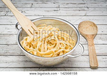 Freshly cooked linguine in a stainless steel colander on a white wood beach table.