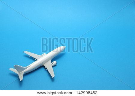 Miniature toy airplane on blue background. Trip by airplane.