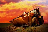 stock photo of power-shovel  - Yellow tractor on golden surise sky - JPG