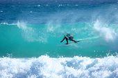 pic of barrel racing  - Surfer racing through a clean blue tube - JPG