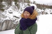 Asian girl in hat and gloves at winter outdoors