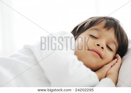 Kid on sleeping bed, happy bedtime in white bedroom